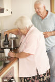 Retired Senior Couple In Kitchen Making Hot Drink Together Royalty Free Stock Images