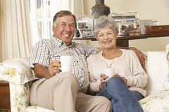 Retired Senior Couple Sitting On Sofa Drinking Tea At Home Together Stock Image