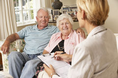Retired Senior Couple Sitting On Sofa Talking To Financial Advisor Royalty Free Stock Images