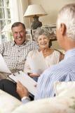Retired Senior Couple Sitting On Sofa Talking To Financial Advisor Royalty Free Stock Image