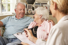 Retired Senior Couple Sitting On Sofa Talking To Financial Advisor Stock Photos