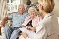 Retired Senior Couple Sitting On Sofa Talking To Financial Advisor Royalty Free Stock Images