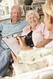 Retired Senior Couple Sitting On Sofa Talking To Financial Advisor Stock Images