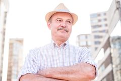 Retired senior hispanic man with hat standing and smiling stock images