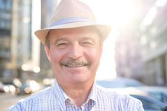 Retired senior hispanic man with hat standing and smiling royalty free stock photo