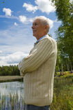 Retired senior by a lakeside Royalty Free Stock Image