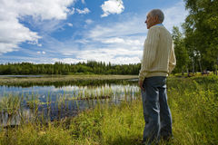 Retired senior by a lakeside. Retired senior in a relaxed posture enjoying a beautiful summertime lakeside view in southern Sweden Royalty Free Stock Images