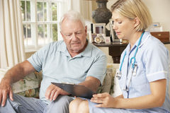 Retired Senior Man Having Health Check With Nurse At Home royalty free stock images