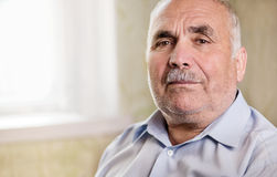 Retired senior man looking pensively at the camera. Retired senior man with a moustache standing looking pensively at the camera, head and shoulders portrait Stock Image