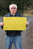 Retired senior man with sign and space for text Stock Photo