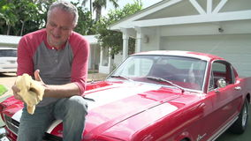 Retired Senior Man Sitting On Hood Of Restored Classic Car. Camera tracks upwards in slow motion showing senior man sitting on bonnet of restored classic car stock video footage