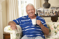 Retired Senior Man Sitting On Sofa Drinking Tea At Home Stock Images