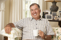 Retired Senior Man Sitting On Sofa Drinking Tea At Home Stock Image