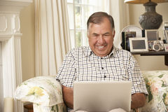 Retired Senior Man Sitting On Sofa At Home Using Laptop Stock Photo