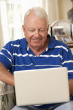 Retired Senior Man Sitting On Sofa At Home Using Laptop Royalty Free Stock Photography