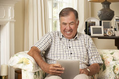 Retired Senior Man Sitting On Sofa At Home Using Tablet Computer Royalty Free Stock Photos