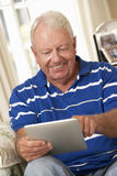 Retired Senior Man Sitting On Sofa At Home Using Tablet Computer Stock Photography