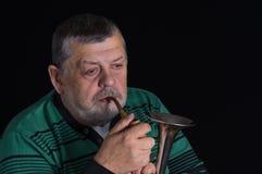 Retired senior man taking trumpet in darkness Stock Photos