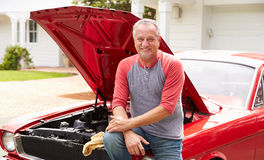 Retired Senior Man Working On Restored Classic Car Stock Image