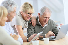 Retired senior people at home having fun using laptop Stock Photography