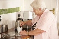 Retired Senior Woman In Kitchen Making Hot Drink Royalty Free Stock Images