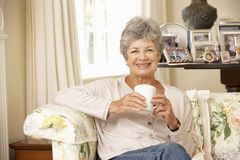 Retired Senior Woman Sitting On Sofa Drinking Tea At Home Stock Image