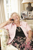 Retired Senior Woman Sitting On Sofa At Home On Phone Stock Photos