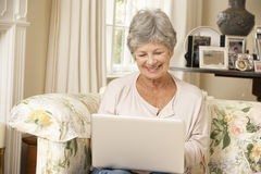 Retired Senior Woman Sitting On Sofa At Home Using Laptop Stock Photography