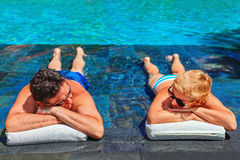 Retired seniors couple relaxing in swimming pool. Successful retirement recreation, summer vacation concept. Retired mature couple enjoying beautiful sunny day Stock Photography