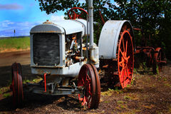 Retired Tractor. An old abandoned deserted McCormick Deering hand crank tractor outlives it's usefulness and sits retired in a field Stock Photo