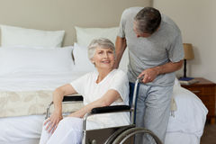 Retired woman. In her wheelchair with her husband Royalty Free Stock Photography