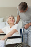 Retired woman. In her wheelchair with her husband Royalty Free Stock Image