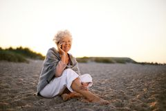 Retired woman in the beach making phone call Stock Image