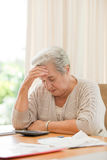 Retired woman calculating her domestic bills Royalty Free Stock Photos