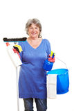 Retired woman with cleaning. Happy retired woman holding many cleaning supplies Royalty Free Stock Photography