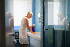 Retired woman doing chores and cleaning bathroom Royalty Free Stock Image