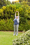 Retired  woman doing her streches in the garden Royalty Free Stock Images