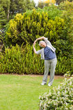 Retired  woman doing her streches in the garden Royalty Free Stock Photo