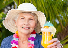 Retired woman drinking a cocktail under the sun Stock Photo
