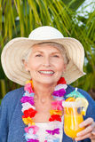 Retired woman drinking a cocktail under the sun Stock Photography