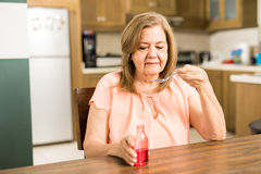 Retired woman drinking a spoon of cough syrup Stock Images