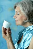 Retired woman drinking tea Royalty Free Stock Images