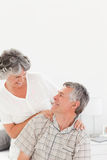 Retired woman giving a massage to her husband Stock Photos
