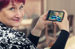 Retired woman is happy at internet dating. 60 years old women is happy on her first internet date. She looks at the camera. Her hands hold mobile phone. On the royalty free stock images