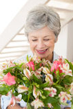 Retired woman holding bouquet of flowers and smiling Royalty Free Stock Images