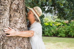 Retired woman hugging a tree Stock Photography