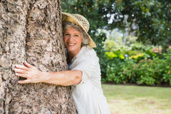 Retired woman hugging a tree smiling at camera Royalty Free Stock Photos