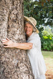 Retired woman hugging a tree and smiling Royalty Free Stock Image