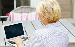Retired woman with laptop Royalty Free Stock Photography