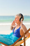 Retired woman listening to music at the beach Royalty Free Stock Photo